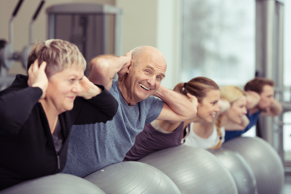 https://f.hubspotusercontent30.net/hubfs/14500231/Elderly%20couple%20doing%20pilates%20class%20at%20the%20gym%20with%20a%20group%20of%20diverse%20younger%20people%20balancing%20on%20the%20gym%20ball%20with%20raised%20arms%20to%20tone%20their%20muscles%20in%20an%20active%20retirement%20concept.jpeg